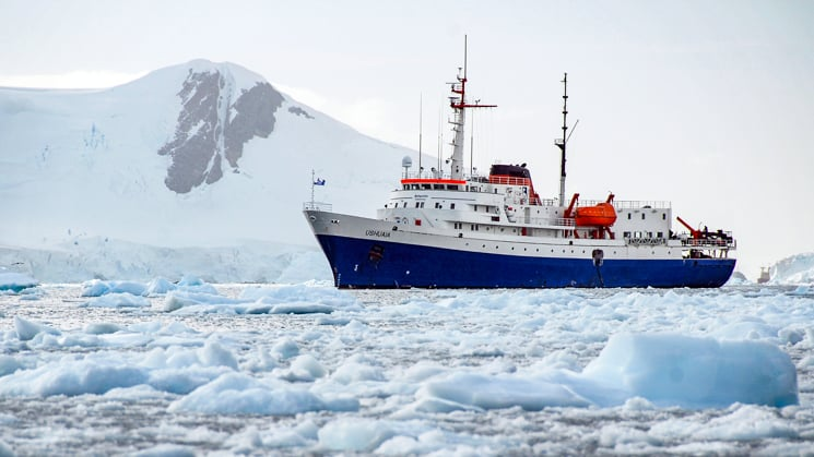 Ushuaia expedition ship port side sailing through icebergs with mountain in background.