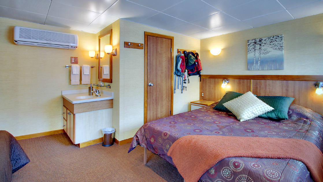 Explorer cabin aboard Wilderness Discoverer with queen bed and sink.