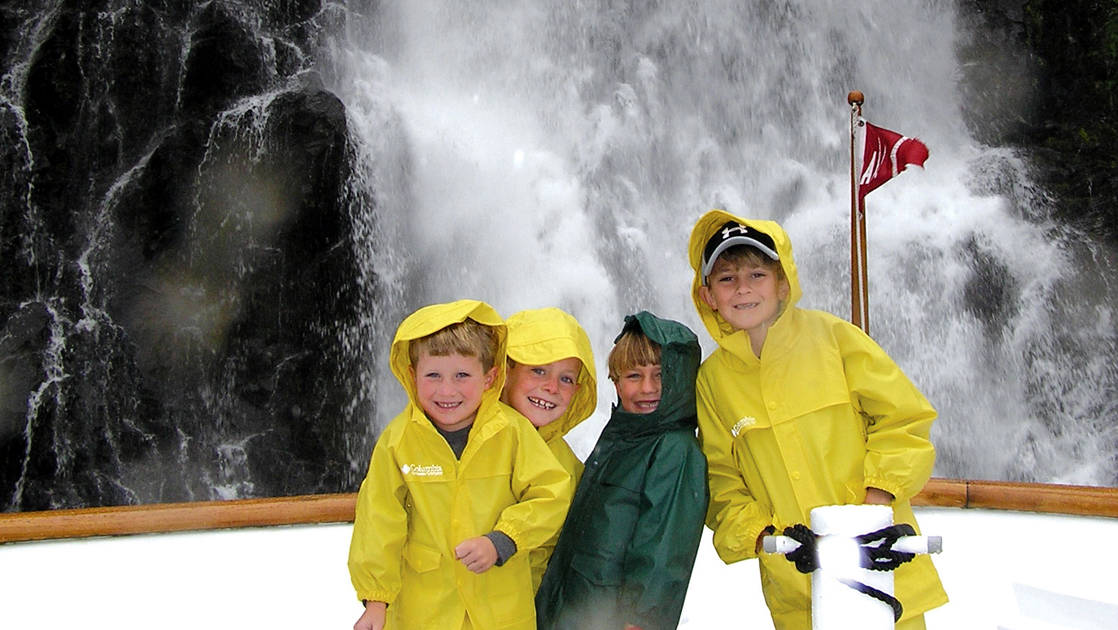 Four kids in rainjackets smiling at the bow of the boat with a waterfall directly behind them while on an Alaska small ship cruise.