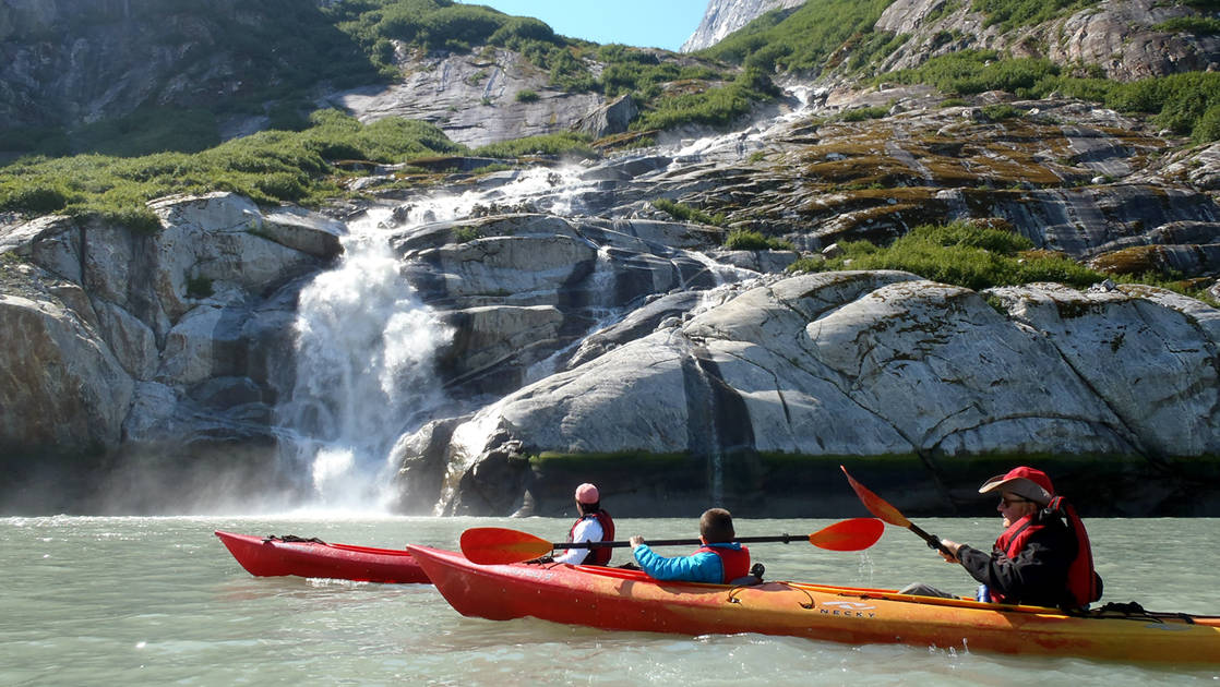 Kayakers kayaking up to a waterfall in Alaska's Northern Passage.