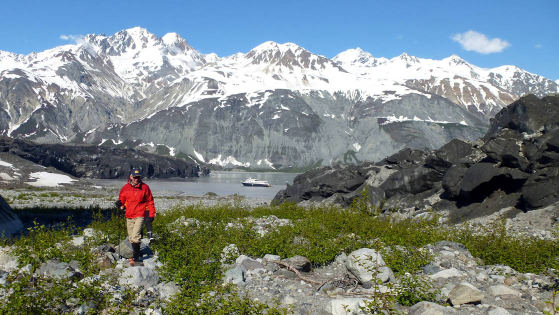 Hiker walking past the shore through Glacier Bay National Park with white-capped mountains and small ship in background.