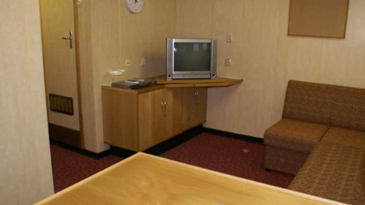 50 Years of Victory mini suite seating area, an L shaped couch with table and TV, with bed, closet, and night stand.