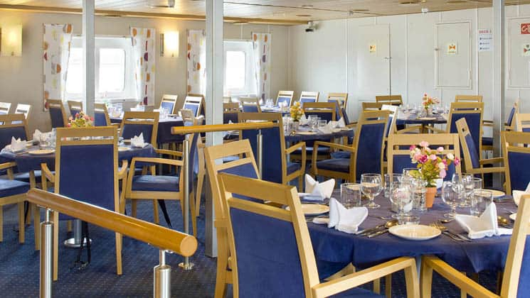 dining room aboard ocean nova small ship filled with tables and chairs