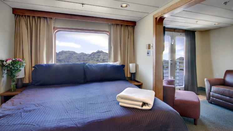 Commodore suite aboard the safari endeavour Alaska small ship, with a large blue bed, adjoining room, and large windows