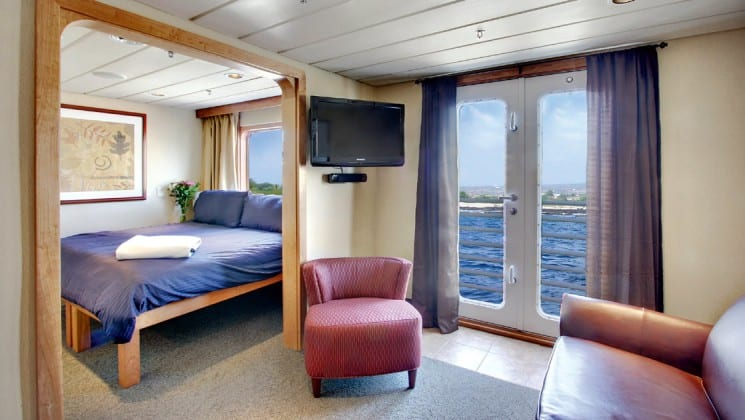Safari Endeavour Alaska small ship Commodore suite with a large open room with glass doors leading to a balcony, a tv and a large bed in the adjoining room