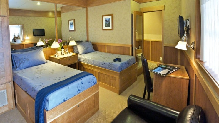 Safari Explorer Hawaii small ship admiral stateroom cabin with 2 beds, comfortable chair, nightstand and opening to an adjoining room