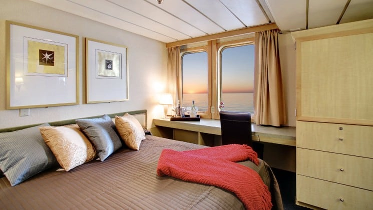 Safari endeavour Alaska small ship admiral cabin with a large bed, two large windows looking at the ocean, and desk