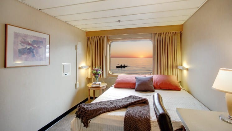 Captain cabin aboard the safari endeavour Baja small ship, with large bed, lamp, and window looking out at the sunset