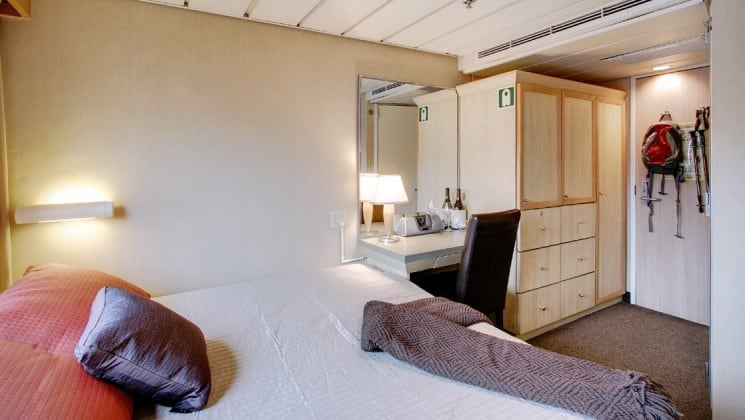 Captain cabin aboard the safari endeavour Alaska small ship, with a large bed, desk, and dresser