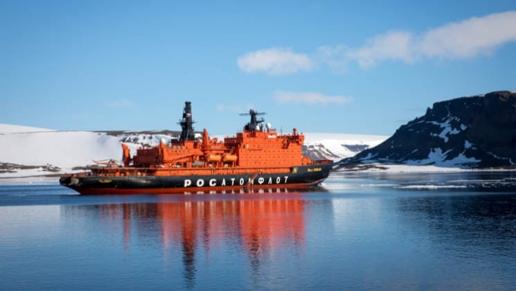 50 Years of Victory sailing in Antarctica with glaciers, mountain range and ice floating on the water.