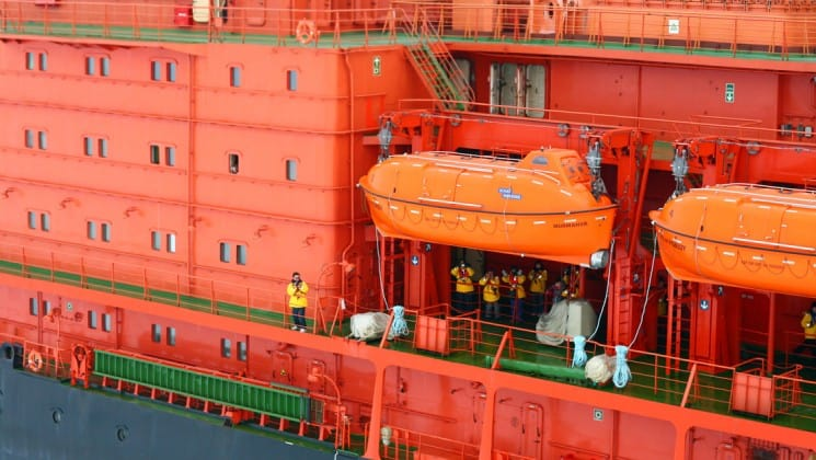 Side view of the orange decks with windows and lifeboats.