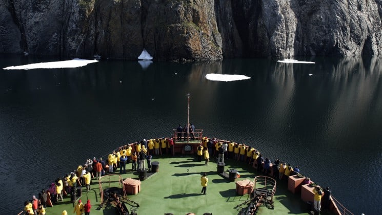 Passengers on the bow deck of the 50 Years of Victory viewing a large mountain range with icebergs floating on the water.