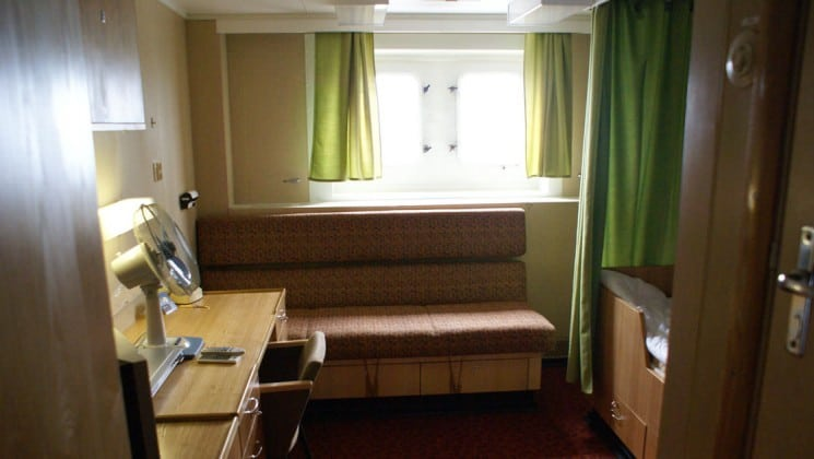 Bench seating with desk, fan, chair twin berth, bathroom and window.