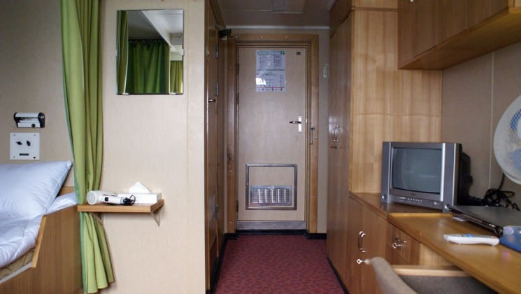 50 Years of Victory twin stateroom with twin berth, bathroom, closet, fan, TV and cabinet space.