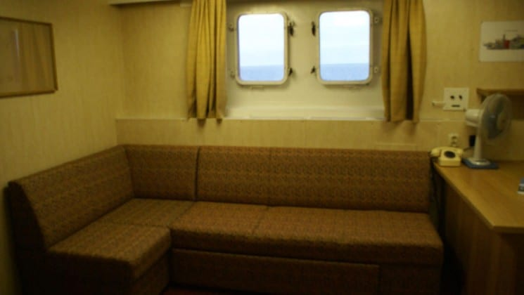 Banquette seating with desk and 2 large portholes in the Victory Suite aboard the 50 Years of Victory.