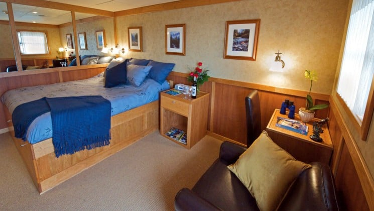 commander stateroom cabin aboard the Safari Explorer Hawaii small ship, with a bed, comfortable chair, large mirror and pictures on the walls