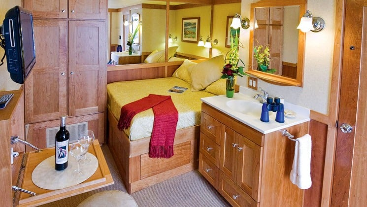 master stateroom with a large bed, mirror behind the bed, nightstand and dresser aboard the Safari Explorer Hawaii small ship