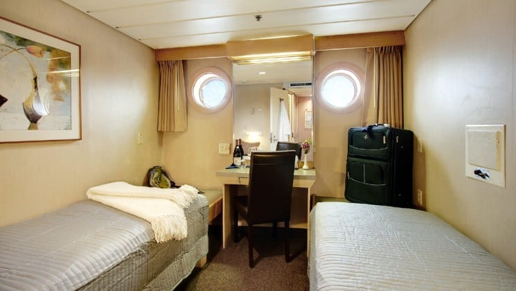 Master cabin with two beds, a desk, and two portholes aboard the safari endeavour Baja small ship