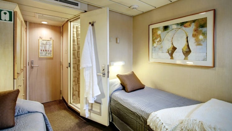Safari endeavour Alaska small ship master cabin with two beds, bathrobe on the wall and picture above the bed