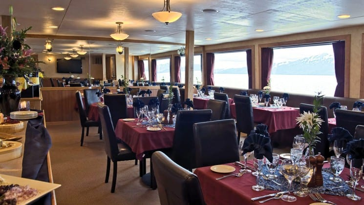 dining room with rows of tables and chairs, lined with windows aboard the Safari Explorer Hawaii small ship