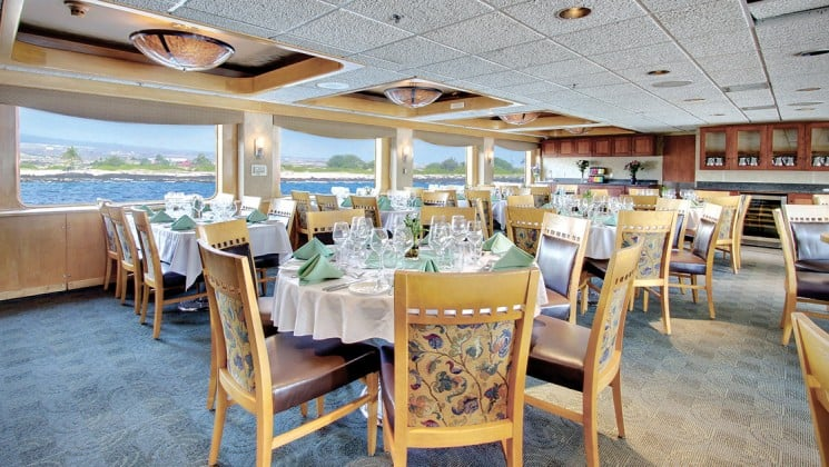 Dining area with a large tables surrounded by chairs and large windows aboard the safari endeavour small Alaska ship