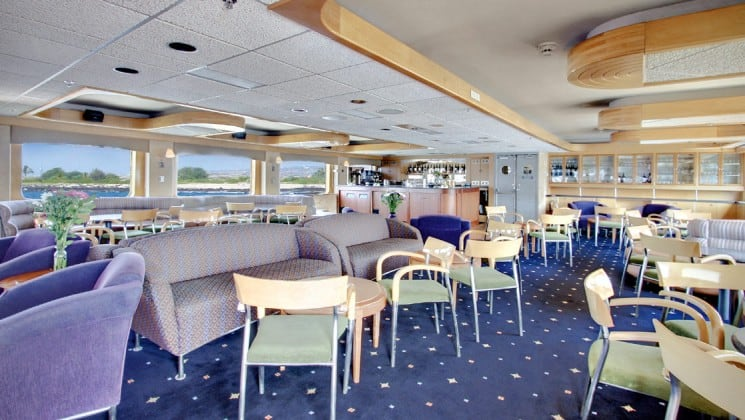 Dining room aboard the safari endeavour baja small ship with rows of chairs and couches and windows