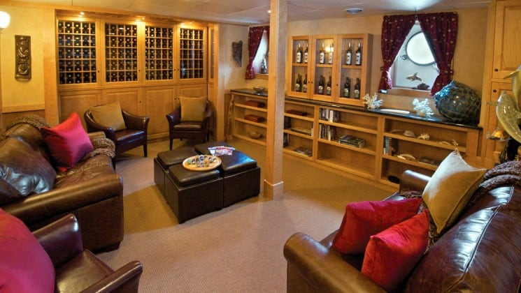 wine library with bottles on the walls and chairs surrounding the room aboard the Safari Explorer Hawaii small ship