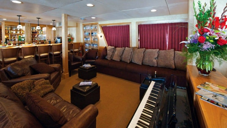 salon with comfortable couch, chairs, ottomans and piano aboard the Safari Explorer Hawaii small ship