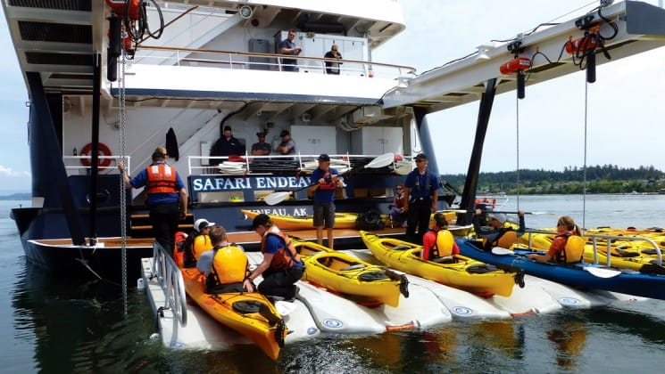 Kayaks and adventure travelers sitting on the back of the safari endeavour small ship in Alaska