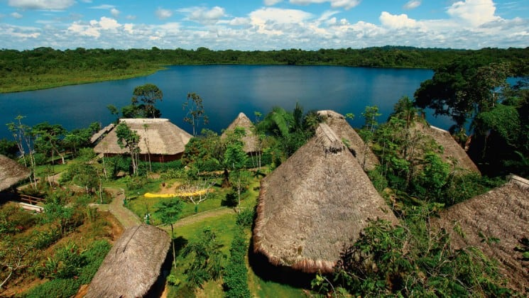Thatched-roof buildings of the Napo Wildlife Center cascade down through the forest toward the blue-green water of a lake and jungle in the distance, at the sustainable, eco Napo Wildlife Center in Ecuador's Amazon