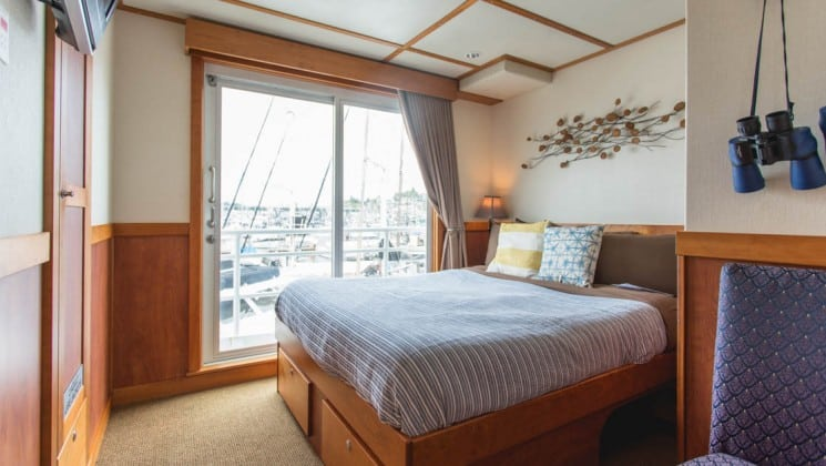 Safari Quest Alaska small ship room with a large bed, decorative metal element above it and a large window behind it