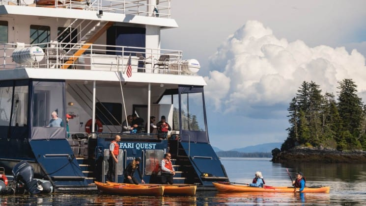 crew and adventure travelers loading kayaks on the back of the Safari Quest Alaska small ship