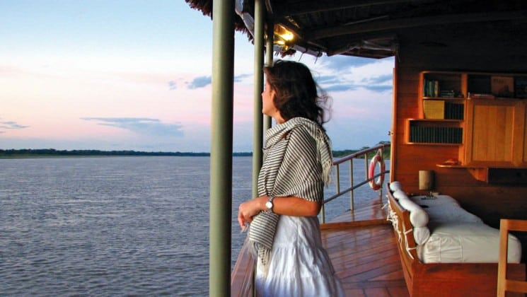 Woman stands at balcony railing of Top Deck and looks upon Amazon River on Delfin II riverboat