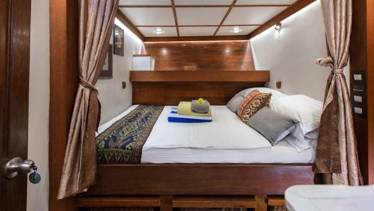Katharina sailboat stateroom with double bed and upper shelf storage.
