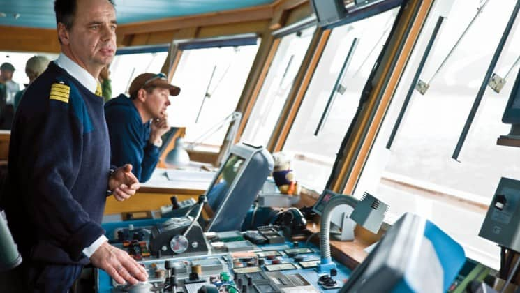 Captain Oliver Kruess at the helm in the bridge of National Geographic Explorer polar expedition ship
