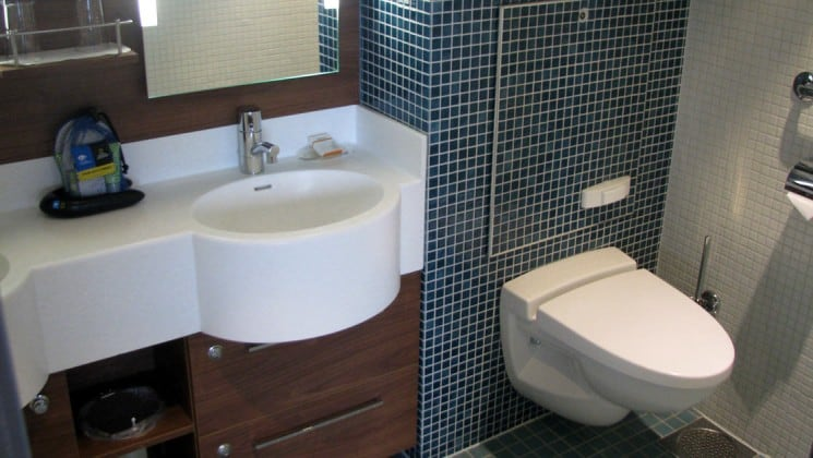 Bathroom with toilet, sink and mirror in Category 6 cabin aboard National Geographic Explorer polar expedition ship