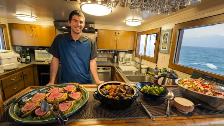 Man in galley with freshly prepared food aboard Discovery classic working yacht in Alaska