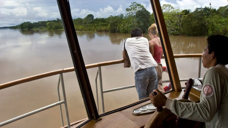 Couple stands at outdoor railing while man in bridge steers vessel aboard Delfin II riverboat on Amazon River cruise