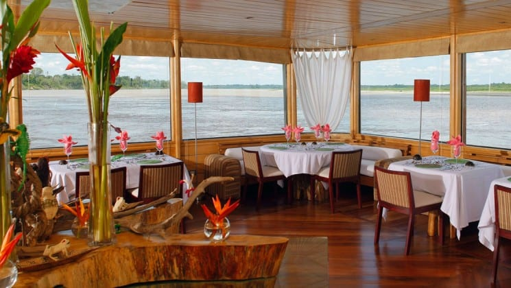 Flowers decorate set tables while large windows show expansive views of the Amazon River aboard the Delfin II riverboat