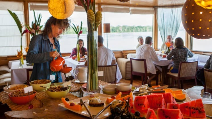 Woman serving herself cereal at breakfast buffet with fresh fruit and pastries as diners sit beneath large windows in Dining Room aboard Delfin II riverboat on Amazon River cruise