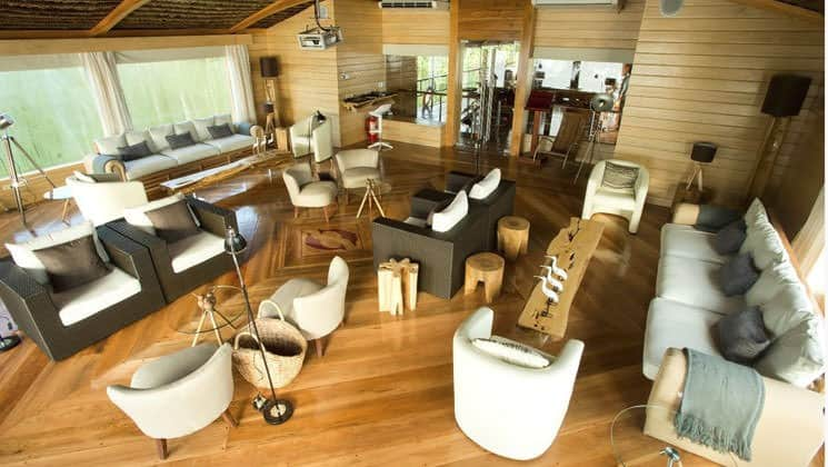 Lecture Room with couches, tables, chairs, lamps, speakers and projector for presentations aboard Delfin II riverboat on Amazon River cruise