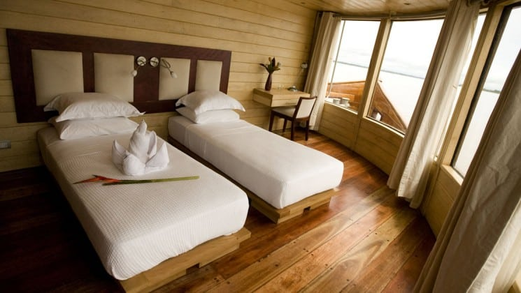 Master Suite with two twin beds, desk, chair and large picture windows aboard Delfin II riverboat on Amazon River cruise