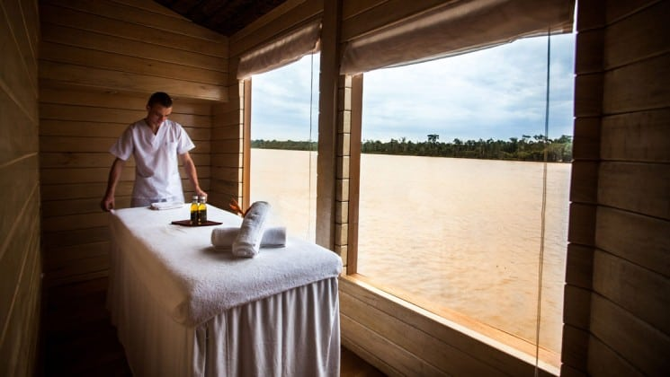 Attendant prepares massage table beside large window in spa aboard Delfin II riverboat on Amazon River cruise