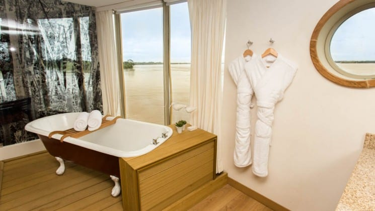 Bathroom with shower, tub, large window and porthole in Master Suite aboard Delfin III riverboat on Amazon River cruise