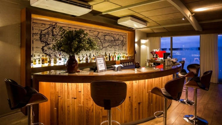 Stools surround a well-lit and well-stocked semicircle bar aboard Delfin III riverboat on Amazon River cruise