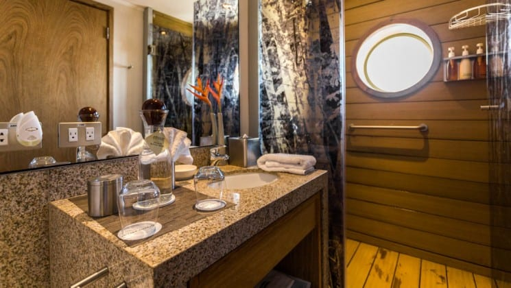 Sink, mirror and shower in bathroom of Corner Suite aboard Delfin III riverboat on Amazon River cruise