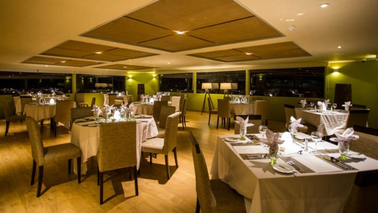 Large windows line the perimeter of the Dining Room with elegant place settings at night aboard Delfin III riverboat on Amazon River cruise