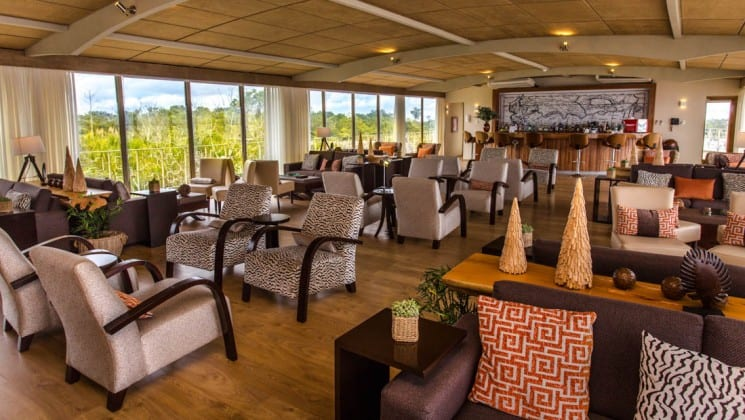 Chairs, couches, tables and bar in large common area with floor-to-ceiling windows aboard Delfin III riverboat on Amazon River cruise