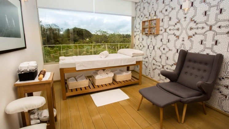 Massage table set up in private room with large window aboard Delfin III riverboat on Amazon River cruise