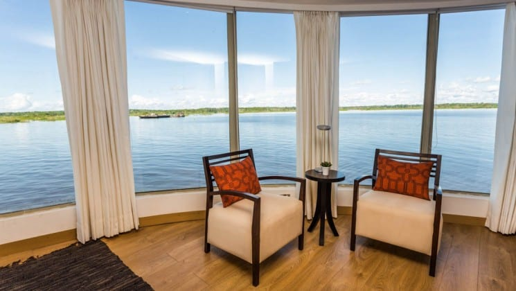 Two chairs and a small table near floor-to-ceiling windows aboard Delfin III riverboat on Amazon River cruise